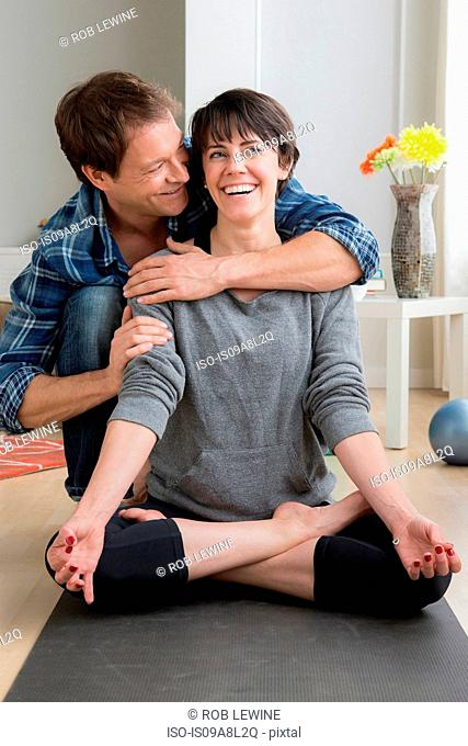Woman doing yoga at home, man hugging her