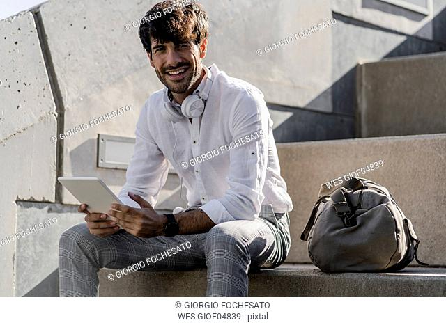 Portrait of smiling young man sitting on stairs outdoors using tablet