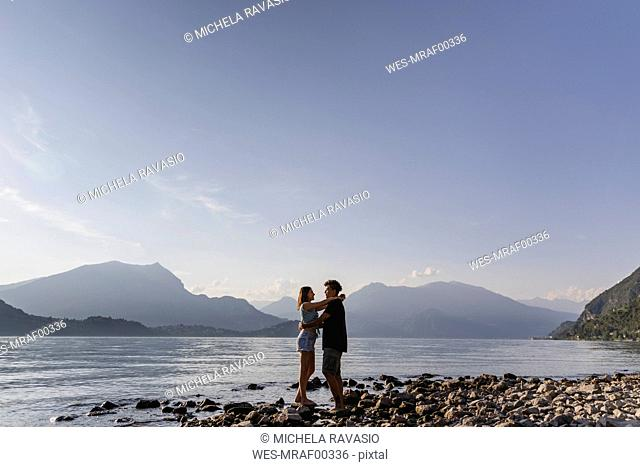 Happy affectionate young couple embracing at the lakeside