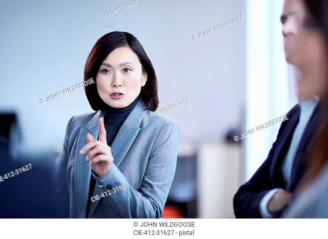 Businesswoman gesturing and explaining in meeting