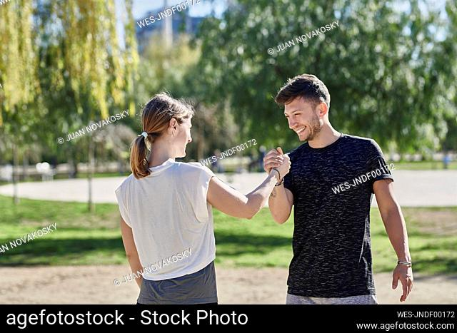 Woman greeting coach before work out in park