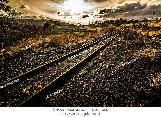 High dynamic range photo of a rural rail line bending around a scenic dawn infrastructure landscape. Summer transport in Avoca, Tasmania, Australia