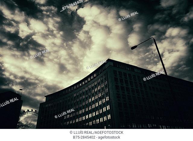 Silueta de un edificio moderno de oficinas y una farola, nubes en el cielo. Londres, UK, Europa