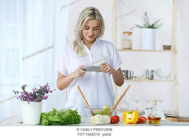 Smiling young woman photographing fresh salad through smart phone at kitchen