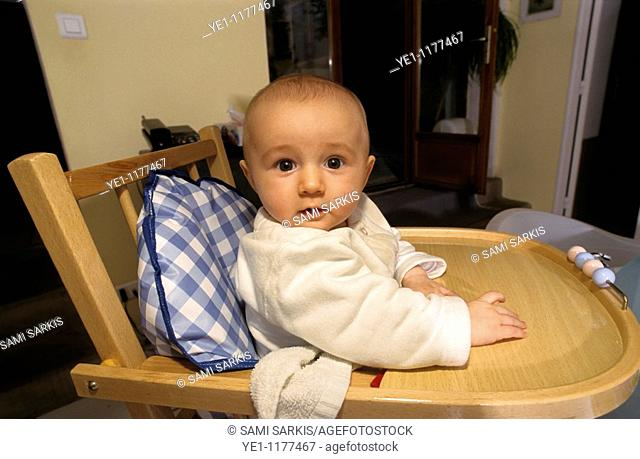 Baby girl sitting on a wooden highchair waiting to be fed
