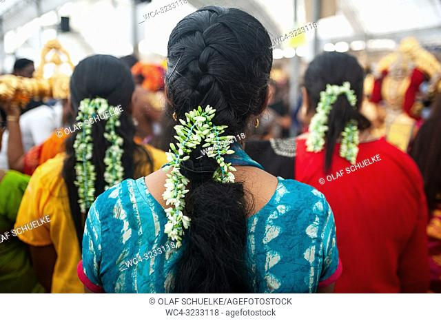 Singapore, Republic of Singapore, Asia - Hindu women wearing traditional floral ribbons during the preparations for the Thaipusam festival at the Sri Srinivasa...