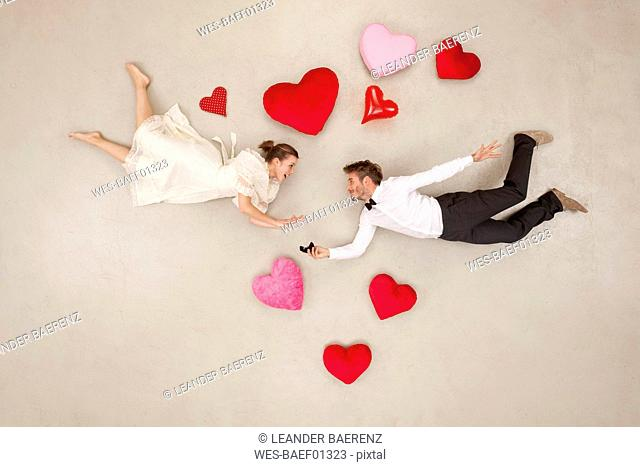 Man proposing to woman with hearts around