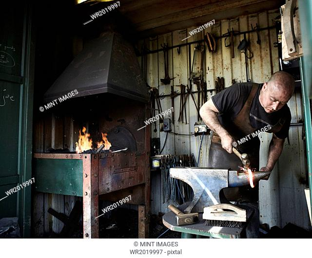 Blacksmith shaping a hot piece of iron on an anvil in a traditional forge with an open fire
