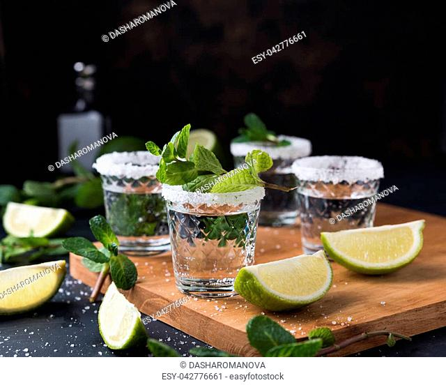 Shooter glasses of vodka or Tequila on black table. Mojito with mint