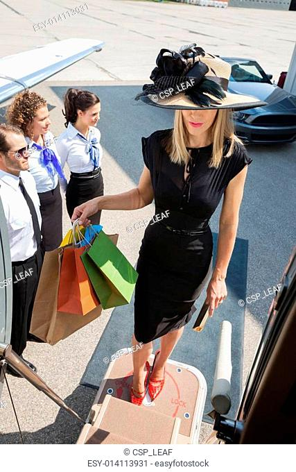 Woman Carrying Shopping Bags While Boarding Private Jet