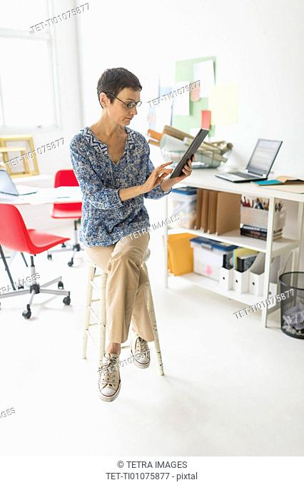 Senior business woman using laptop and tablet in office