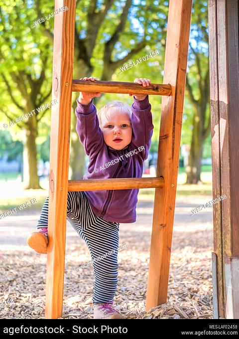 Portrait of toddler girl climbing on ladder at playground
