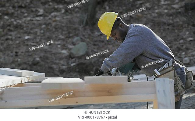 Carpenter using a circular saw for a bevel cut on dormer rafter