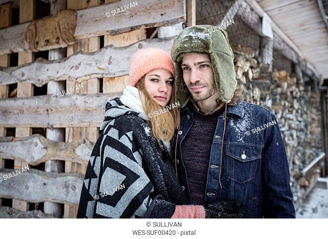 Portrait of couple in front of wood pile outdoors in winter