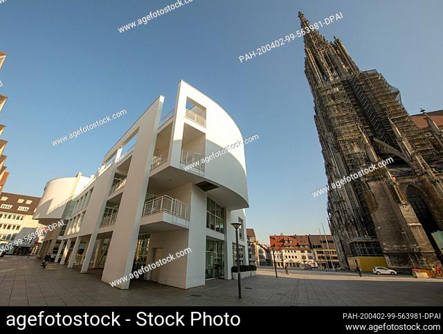 02 April 2020, Baden-Wuerttemberg, Ulm: Few people walk across the central Münsterplatz with the townhouse, and the corona crisis has brought life in the city...