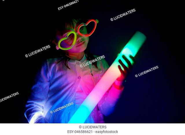 Little girl (age 6) play with colorful lights in the dark