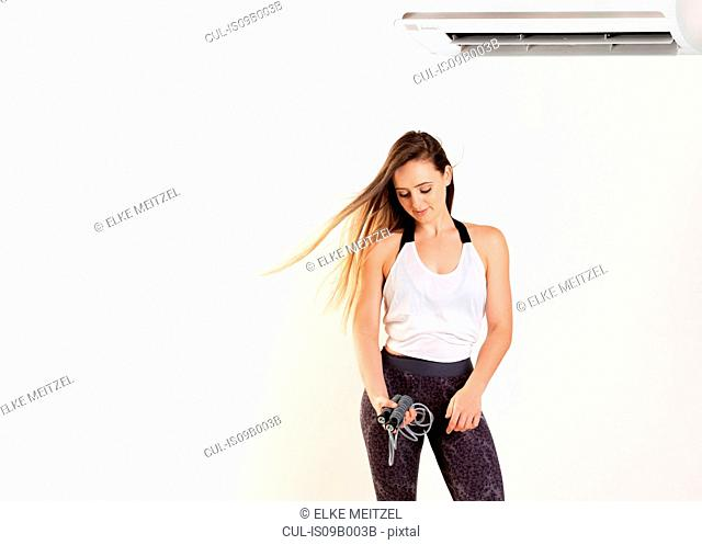 Woman holding resistance band under air conditioner, white background