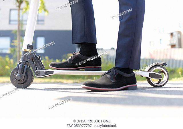 young businessman with electric scooter outdoors