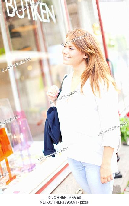 Smiling young woman looking at shop window, Vaxjo, Smaland, Sweden