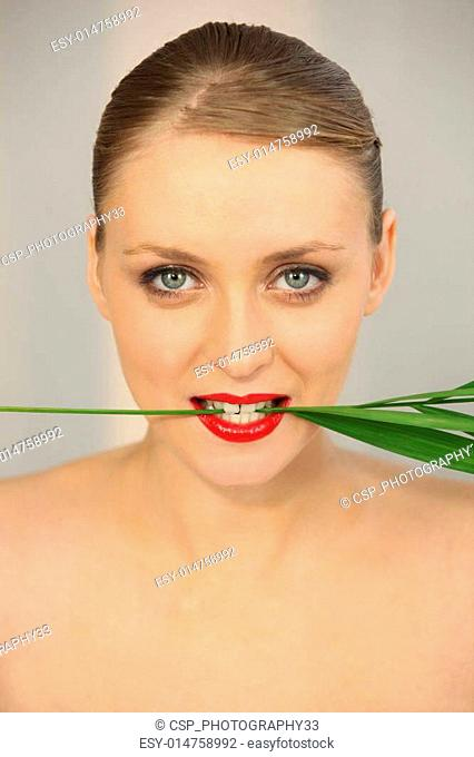Woman holding a stem in between her teeth