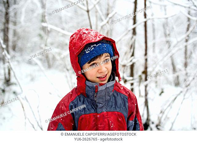 Portrait of little boy in the forest while snowing