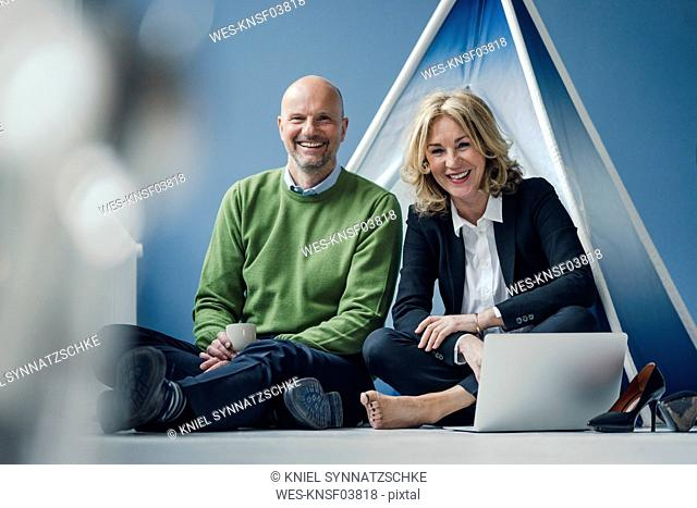 Happy businessman and businesswoman sitting at teepee indoors with laptop