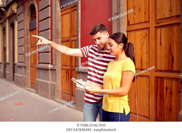 Young couple studying a map and pointing to their front while smiling satisfied and dressed casually in t-shirts with old buildings behind them