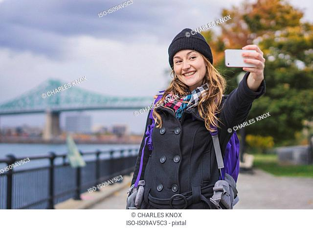 Young woman taking self portrait using smartphone, Ile Ste-Helene, Montreal, Quebec, Canada