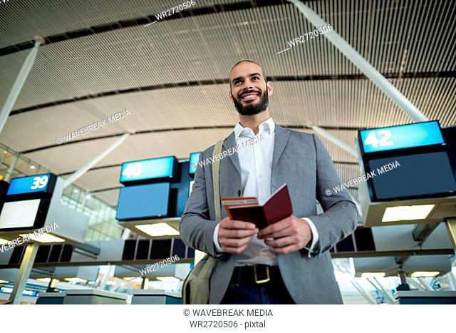 Smiling businessman holding a boarding pass and passport