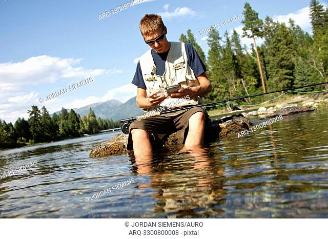 A teenage boy sits on a rock as he chooses a fly while fly fishing on the Swan River near Bigfork, Montana