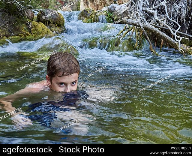 Boy looking at camera while is sumerged on a mountain river. Villahermosa river, Ludiente, Castellón, Spain