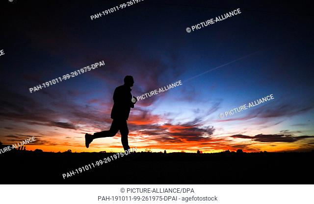 11 October 2019, Baden-Wuerttemberg, Stuttgart: The evening sky over Stuttgart shines in beautiful colours while a jogger walks by