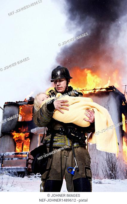 Fireman holding rescued girl, burning building in background