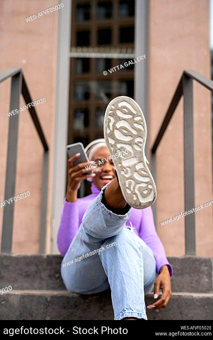 White haired woman with white headphones listening to music in the city, showing her sole of shoe