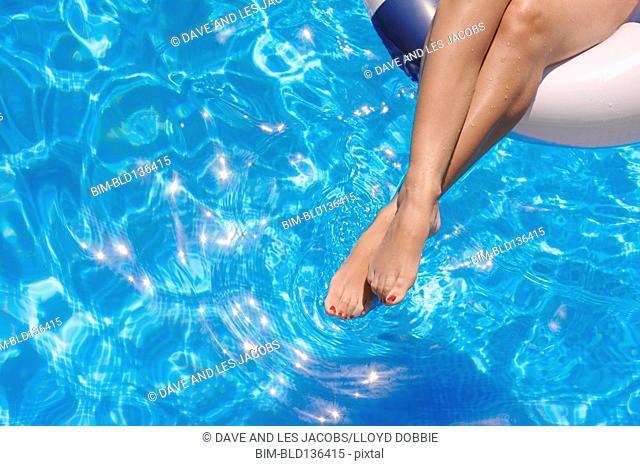 Hispanic woman's legs relaxing in swimming pool