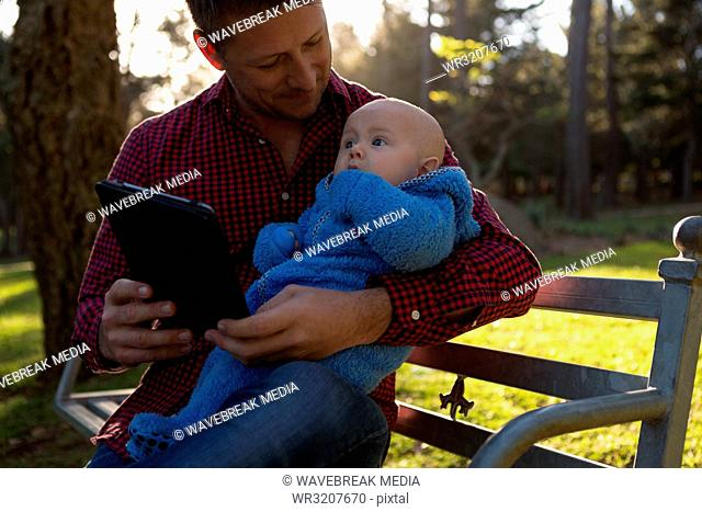 Father and baby boy using digital tablet in the park
