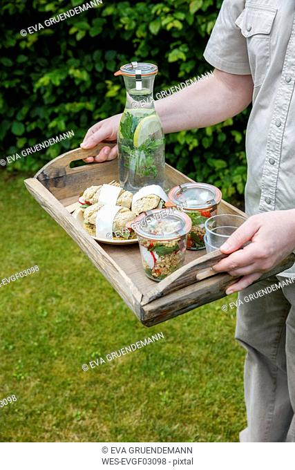 Person carrying tray with vegetarian snacks for picnic
