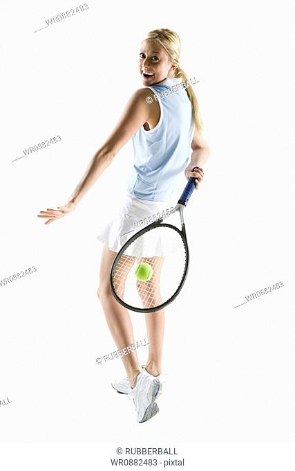 Rear view of a young woman playing tennis