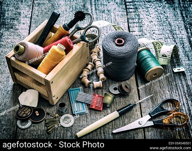 The concept of sewing accessories. Sewing tools and accessories for sewing threads, spools, scissors, buttons, needles, pin and tailor meter on an old wooden...
