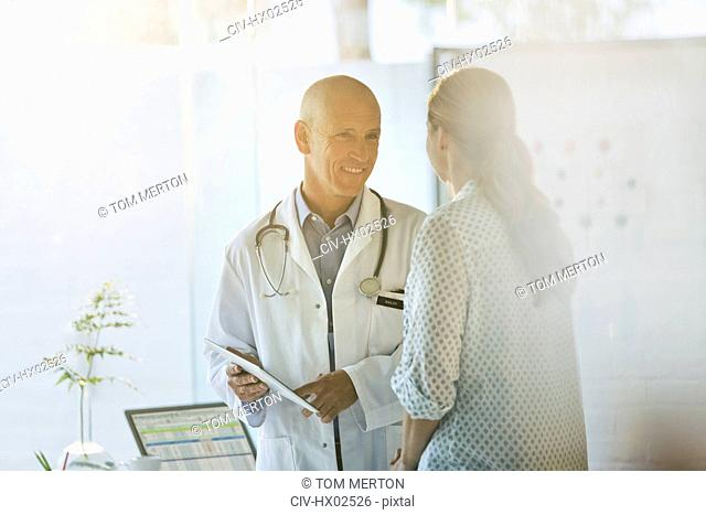 Smiling male doctor showing digital tablet to female patient in doctor's office