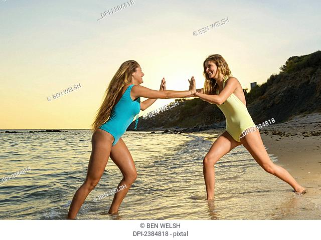 Two young women in bathing suits playing on the beach at sunset; Tarifa, Cadiz, Andalusia, Spain