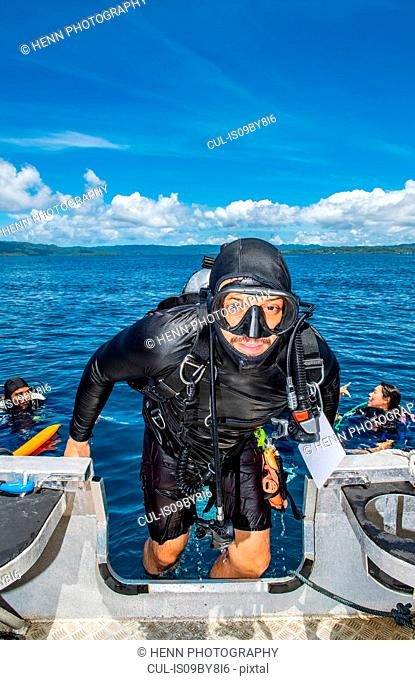 Scuba divers boarding dinghy after a dive, portrait, Raja Ampat, Sorong, Nusa Tenggara Barat, Indonesia