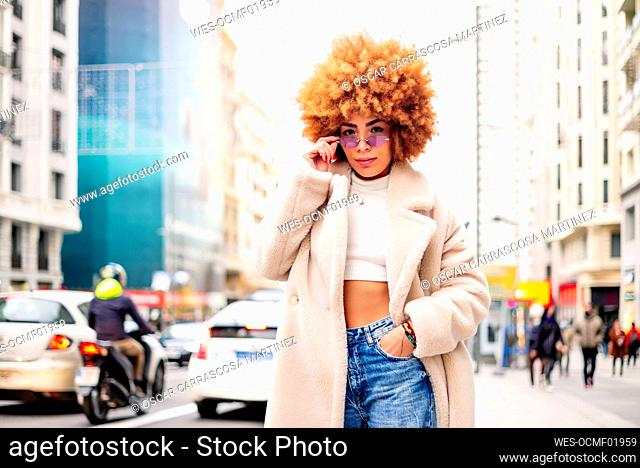 Stylish woman with blond hair wearing sunglasses standing on street