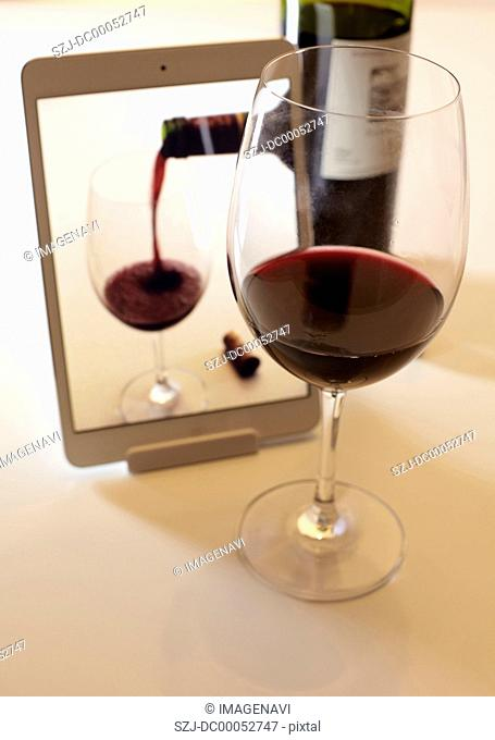 Glass of red wine and a tablet PC