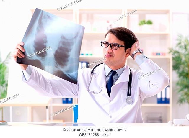 Young doctor looking at x-ray images in clinic