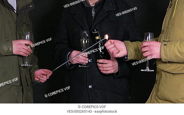 3 men chatting and celebrating new years eve, whilst lighting a sparkler and drinking champaign