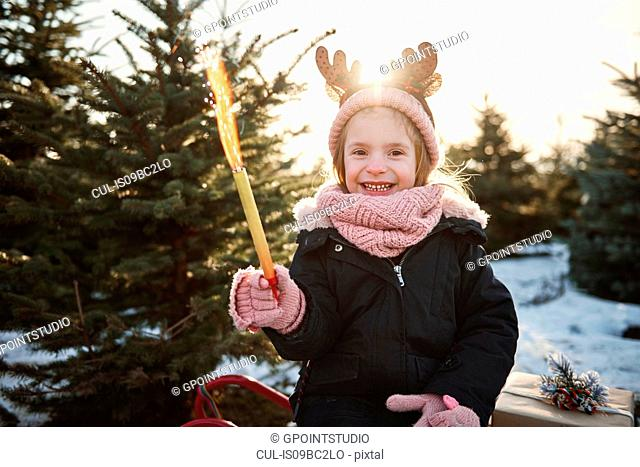 Girl in christmas tree forest wearing antlers, portrait