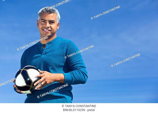 Mixed race man playing soccer outdoors