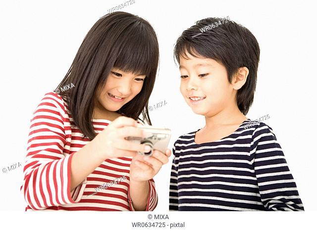 Boy and girl looking digital camera