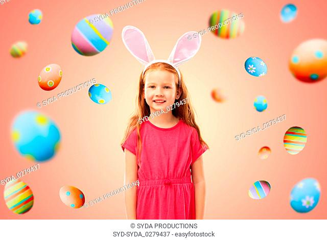happy red haired girl wearing easter bunny ears
